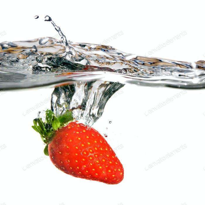 Frische Erdbeere fallen in Wasser mit Splash isoliert auf Whit