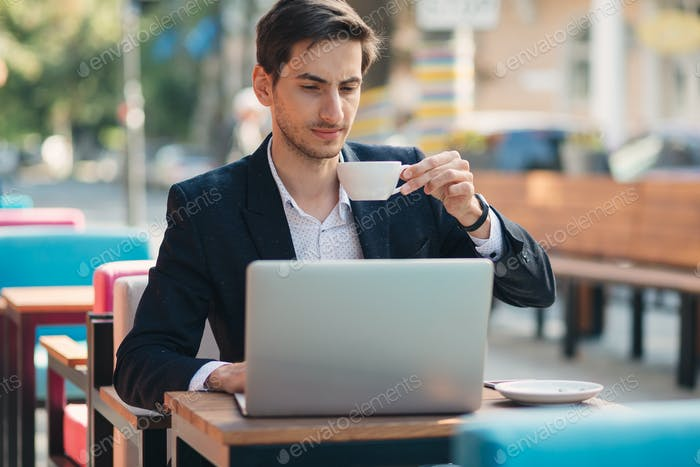 Freelancer, in casual jacket, unbuttoned with laptop and coffee