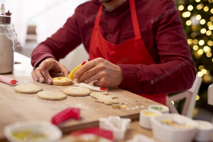 Man decorating cookies in the kitchen