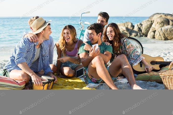 Freunde lachen beim Sitzen am Ufer