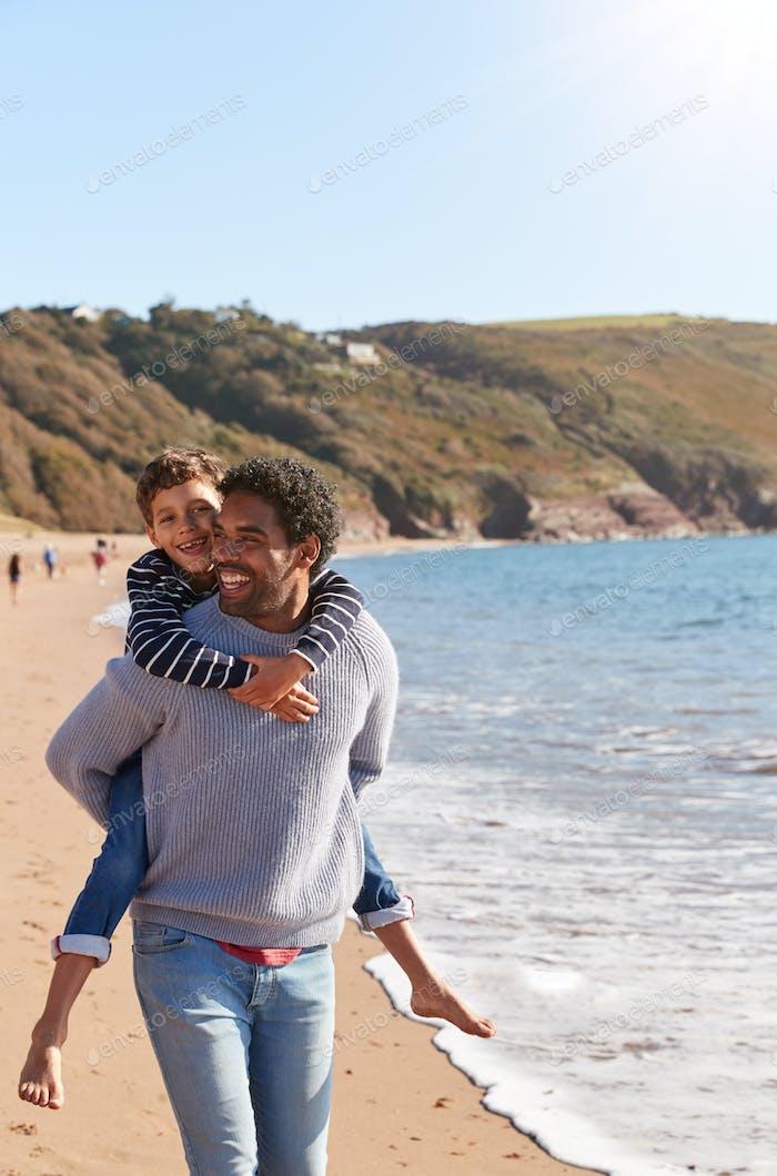 Liebevolle Vater geben Sohn Huckepack als Sie gehen entlang Winter Strand zusammen