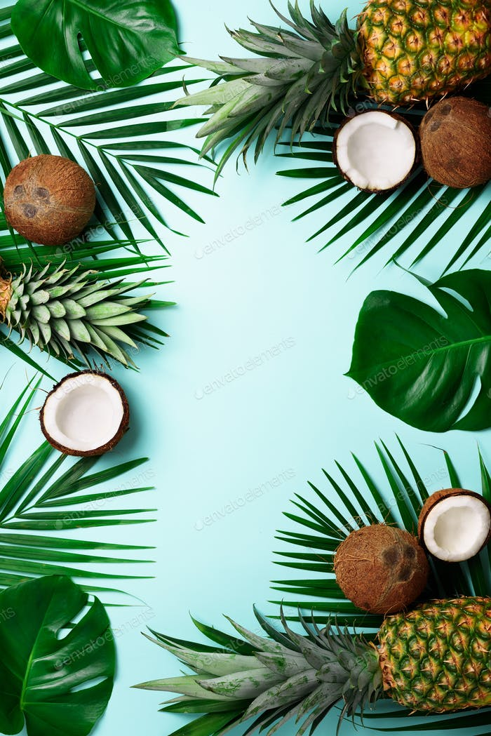 Exotic pineapples, ripe coconuts, tropical palm and green monstera leaves on blue background with
