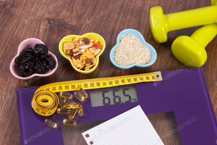 Tape measure on digital scale, tablets, dumbbells and muesli, healthy food and slimming concept