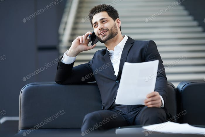 Confident mixed race businessman discussing contract on phone
