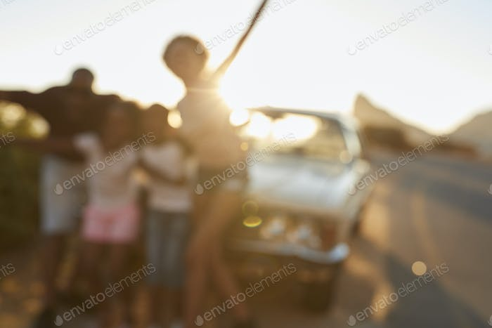 Defocused Portrait Of Family Standing Next To Classic Car