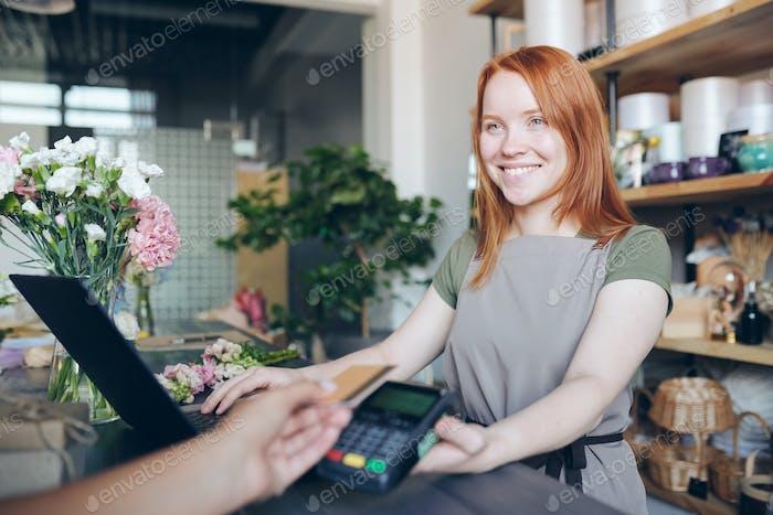 Girl selling flowers in shop
