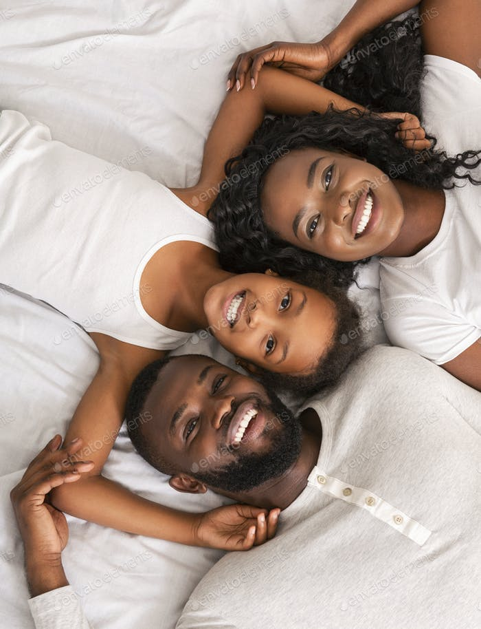 Top view of happy black family lying in bed together