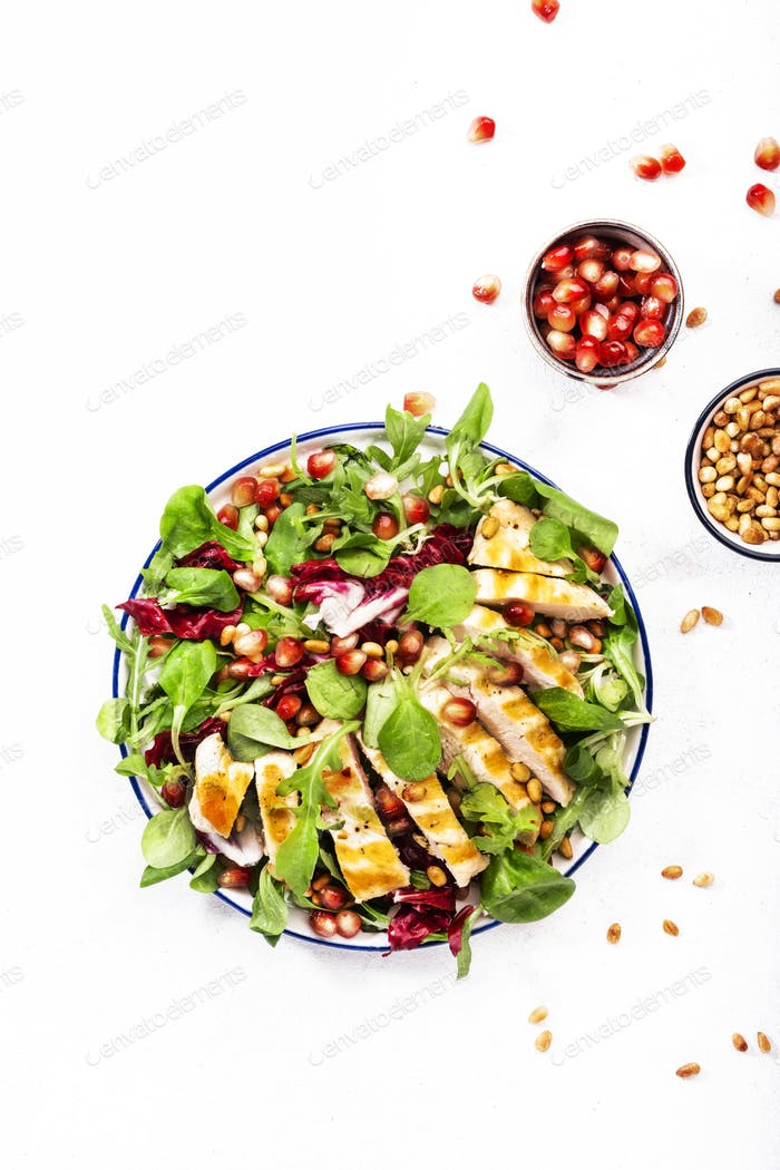 Salad with chicken breast, spinach, arugula, cedar nuts and pomegranate