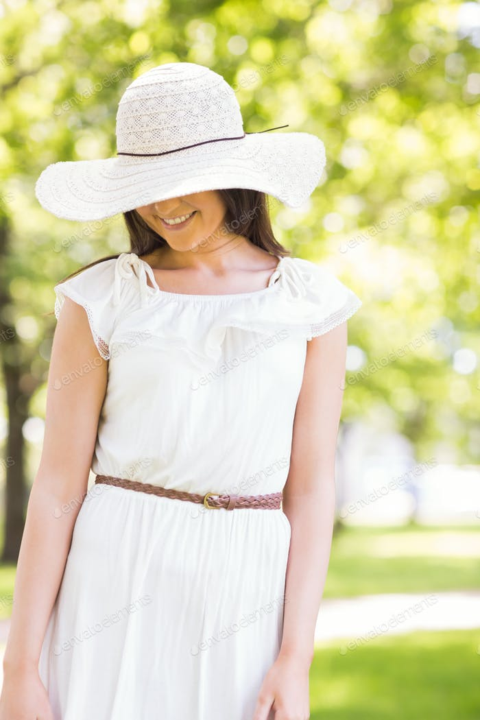 Happy young woman in sun hat standing on grassland in park