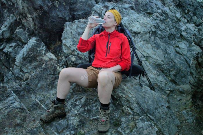 female hiker drinking water