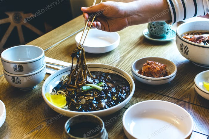 Man eating Korean noodles in thick sweet soy sauce with chopsticks