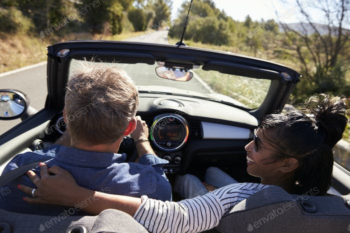 Couple driving in car, woman looks at her partner, back view