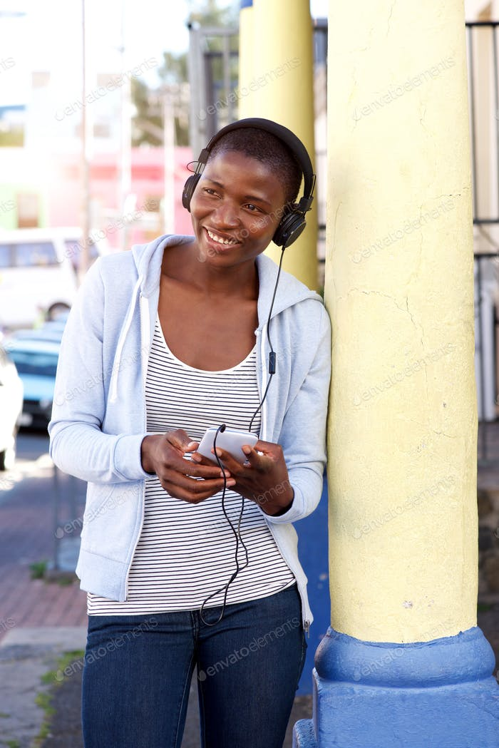 Portrait of happy woman outside listening to music