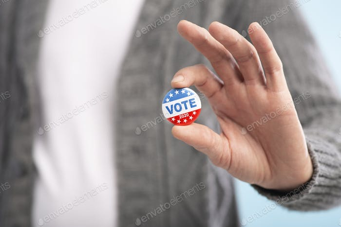 Law abiding american citizen holding vote button in hand