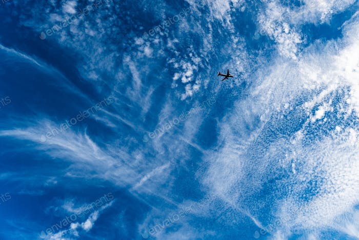 Blue sky with white stretched clouds and passenger plane flying high.