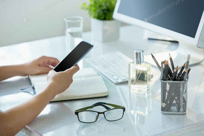 Close-up of female hands using smart phone while working on computer at modern office interior