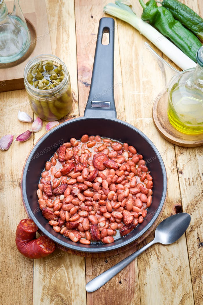 beans with chorizo stewed in metal frying pan