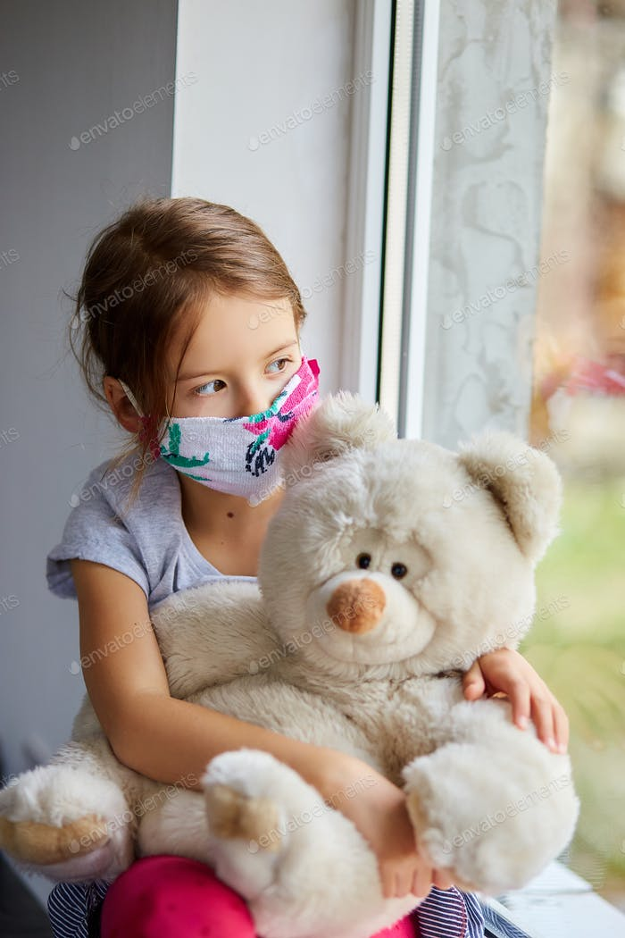 Little girl, child in mask with teddy bear sits on windows, coronavirus quarantine