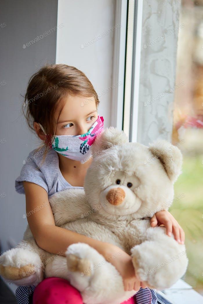 Little girl, child in mask with teddy bear sits on windows, coronavirus quarantine