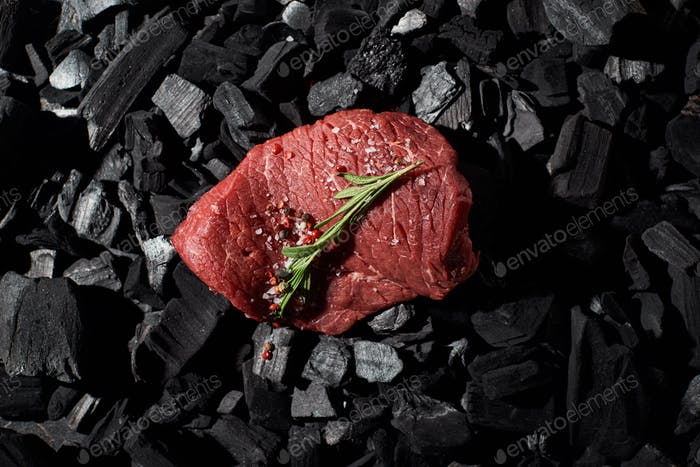 Top View of Raw Beef Steak With Rosemary, Salt And Pepper on Charcoals