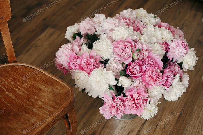 Big stylish peony bouquet in metal bucket on rustic wooden floor