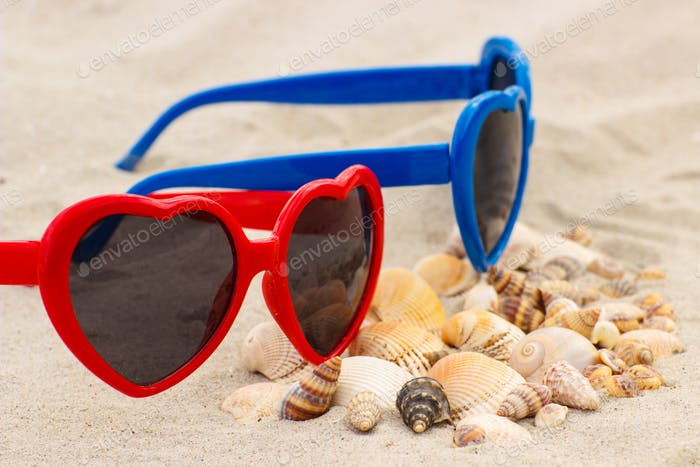 Heap of shells and sunglasses on sand at beach, concept of summer and vacation time