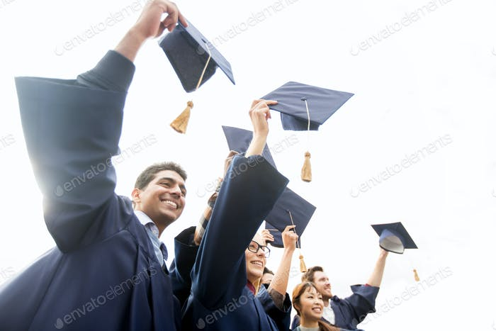 happy students or bachelors waving mortar boards