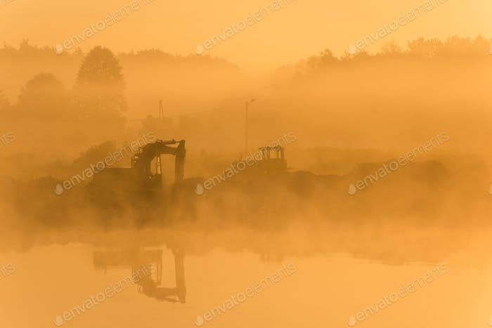 Sunrise over lake with mining vechicles