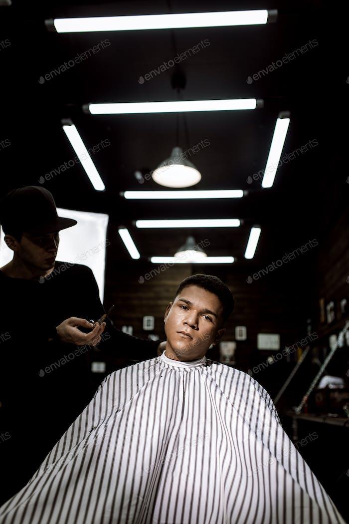 Стильная парикмахерская. Мода парикмахер делает стильную прическу для черноволосый человек сидит