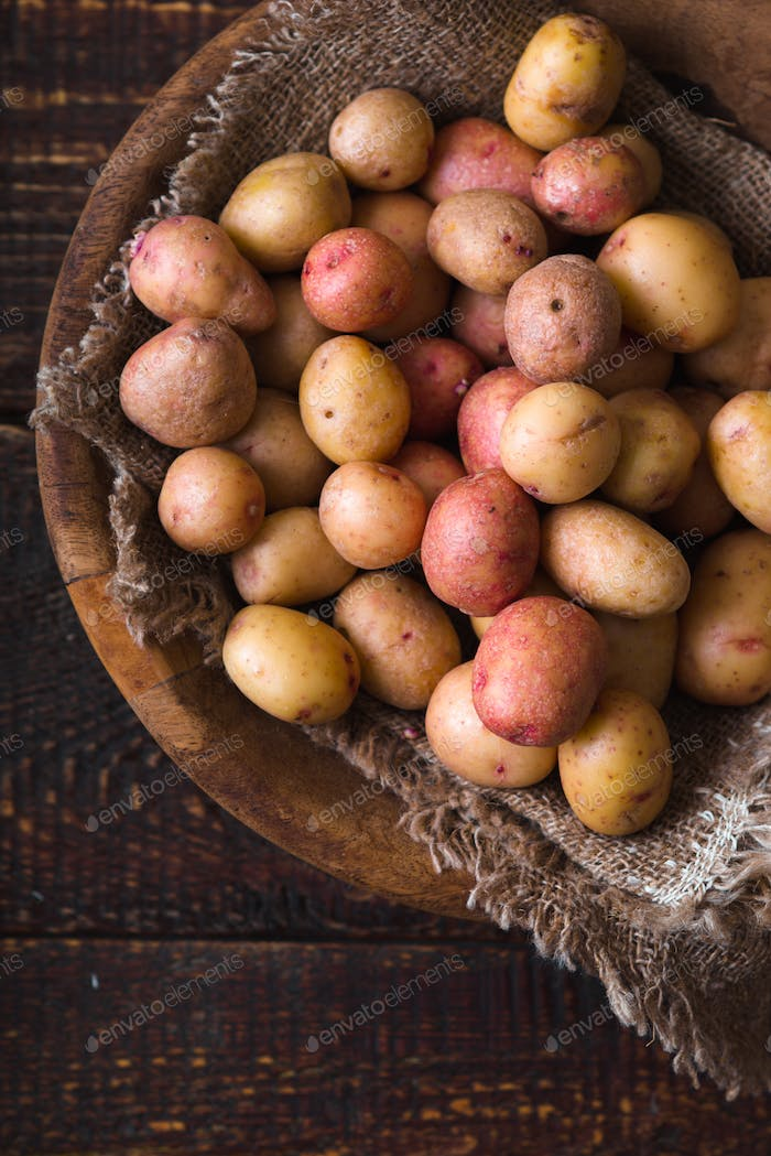 Raw potatoes red and white in a wooden bowl