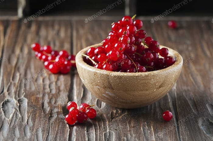 Macro photo of red currant on the wooden table
