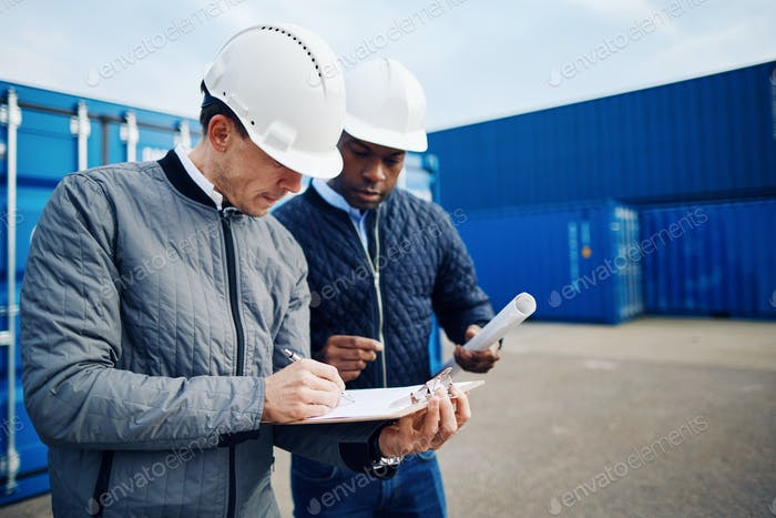 Two engineers standing in a shipping yard discussing logistics