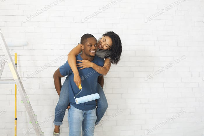 African american millennial couple on white brick wall background