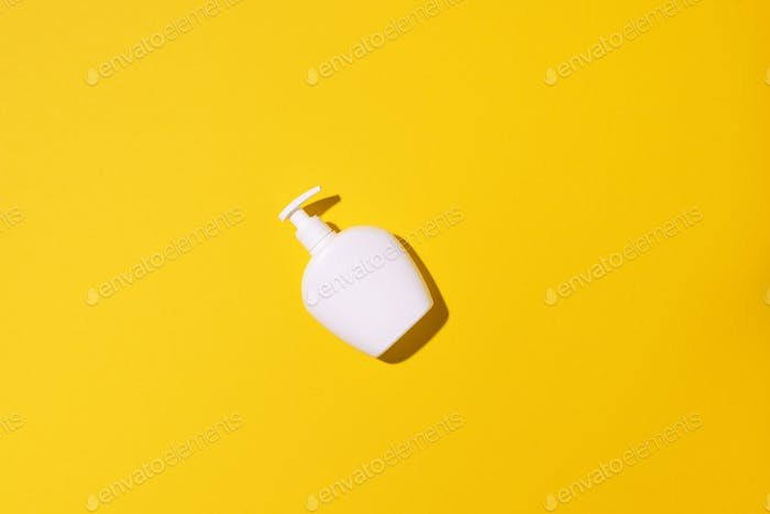 Shampoo and soap bottles on yellow background. Top view. Flat lay. Copy space