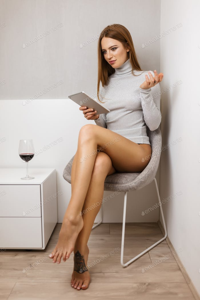 Pretty girl in sweater sitting in chair thoughtfully looking in tablet with glass of red wine
