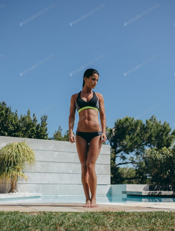 Beautiful young female in swimwear by the poolside