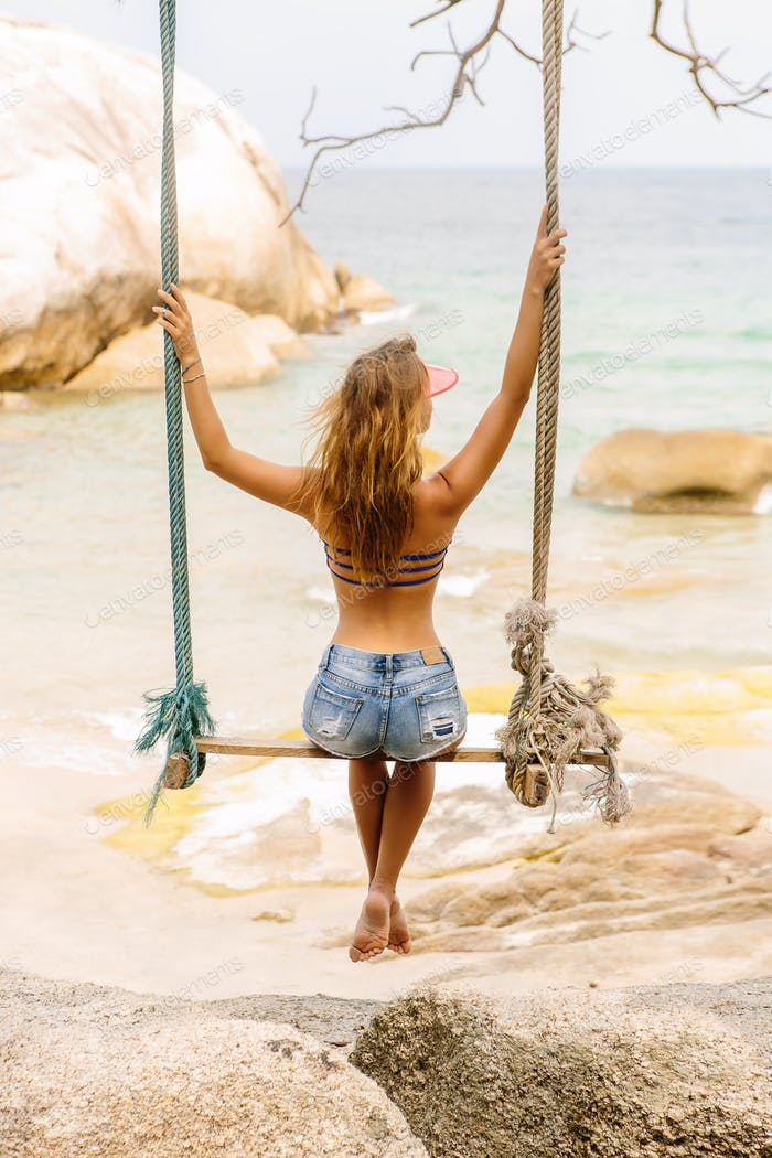 Beautiful woman on swing in tropics.