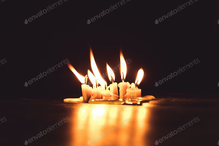 close-up view of burning candles and reflection in darkness