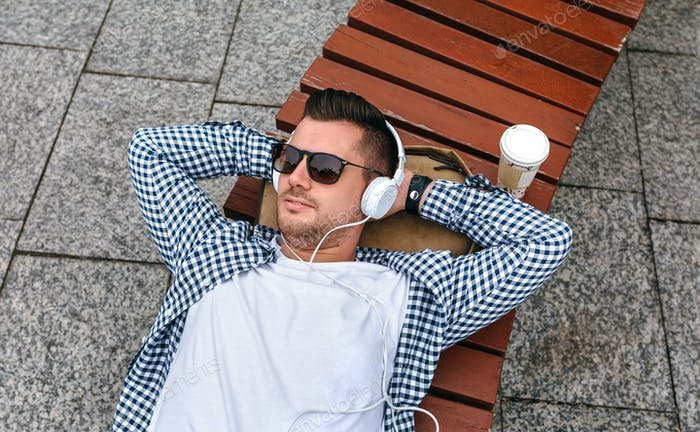 Man with headphones lying on a bench