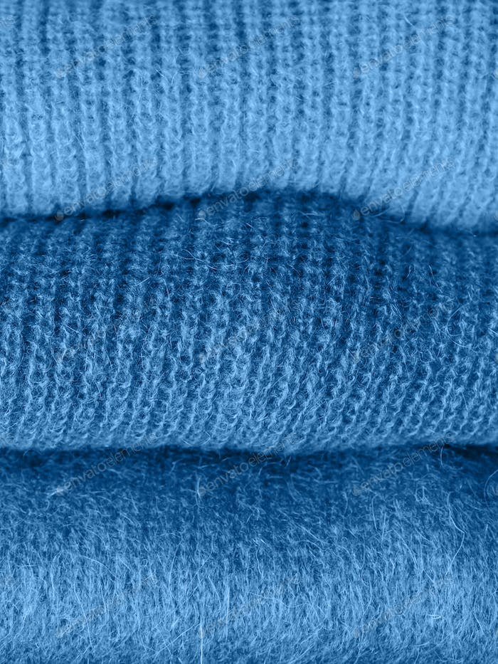 Pile of classic blue color woolen sweaters