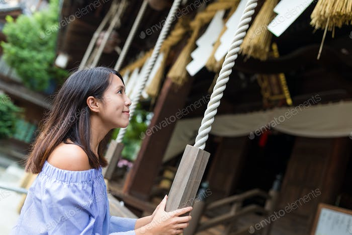 Woman holding the rope in Japanese temple