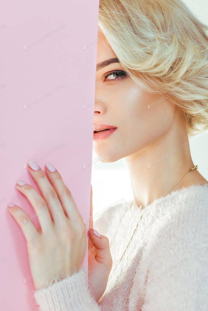 schönes blondes Mädchen mit rosa Banner blickt in die Kamera auf grau
