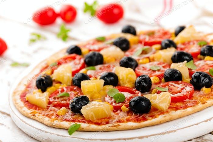 Pizza mit Tomaten, Mozzarella-Käse, Oliven, Mais und Basilikum. Traditionelle italienische Küche