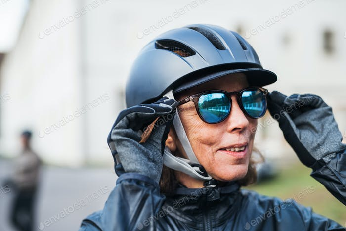 An active senior woman with bike helmet standing outdoors, putting on sunglasses.
