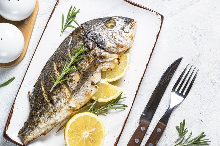 Baked dorado fish with lemon and rosemary top view