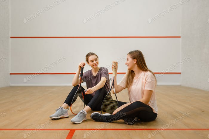 Two players with squash rackets sits on floor