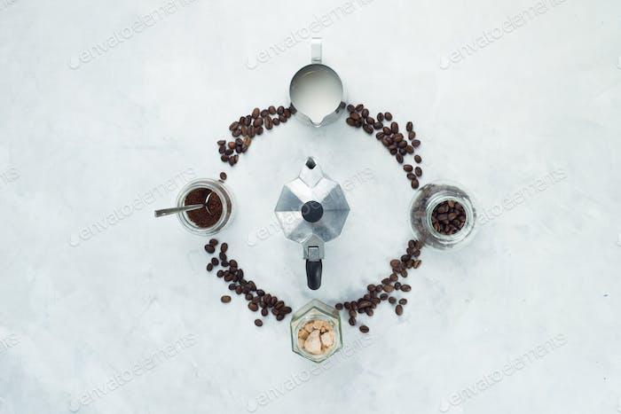Kaffeebohnen Kreis mit Mokkakanne, Geysir Kaffeemaschine, Milchkännchen, gemahlenem Kaffee und Zucker.