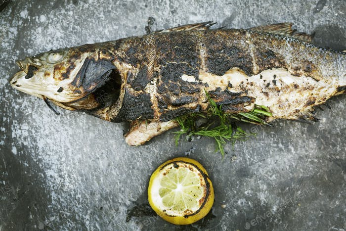 High angle view of a grilled fish with lemon and herbs.