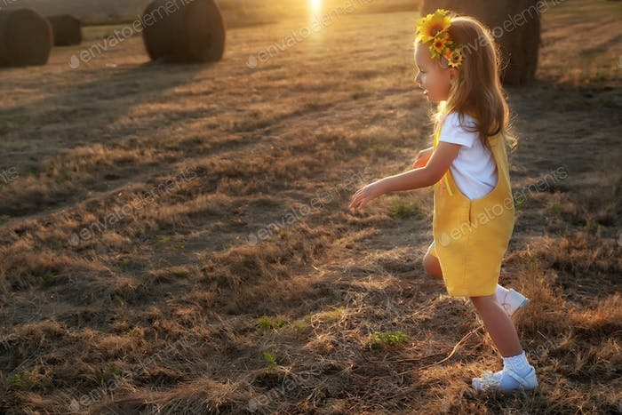 Happy girl child in yellow dress runs in autumn field