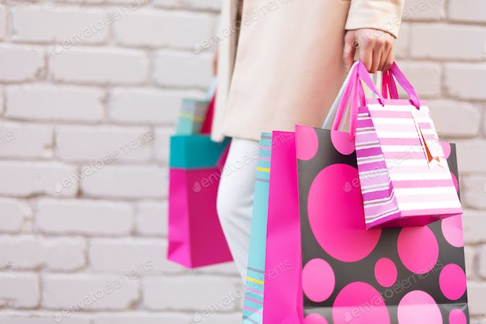 Pink flowers in female hands and shopping bags on brick background. Birthday, Mother's, Women